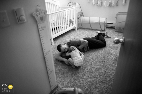 A father lays on the floor with his baby in this Family Photojournalist Association contest awarded photo created by a Seattle, WA family photographer.