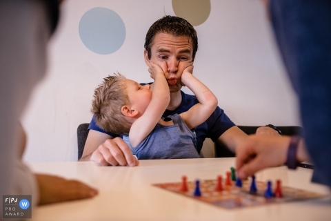 A young boy squeezes his father's cheeks as people sit at a table playing a game in this photo by a Netherlands family photojournalist.