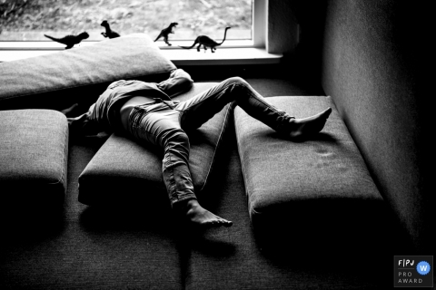 A child plays with cushions as toy dinosaurs stand lined up on the window sill in this black and white photo by a Copenhagen, Denmark family photojournalist.