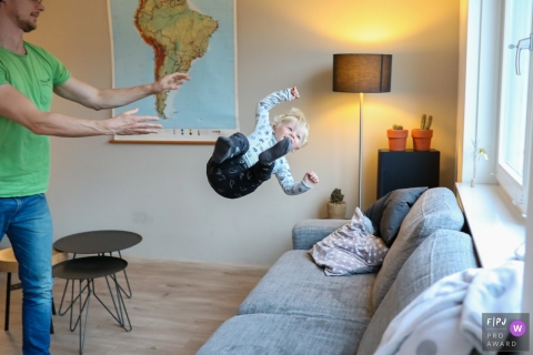A boy is midair as his father tosses him onto a couch in this photo by a Netherlands family photojournalist.