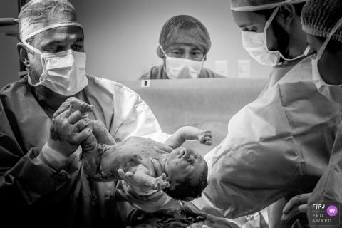 Un médecin tient un nouveau-né à l'hôpital immédiatement après sa naissance sur cette photo en noir et blanc d'un photographe de naissance d'Espirito Santo, Brésil.