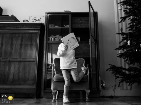 A child covers their face with a book with a large baby face on the cover in this black and white photo by an Antwerpen family photojournalist.