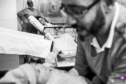 A mother looks across the hospital room where her husband hods their newborn in this black and white photo by a Sao Paulo birth photographer.
