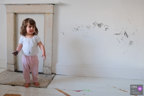 A little girl stands next to a white wall covered in hand prints with paint on her hands in this photo by a Gloucestershire, England family photojournalist.