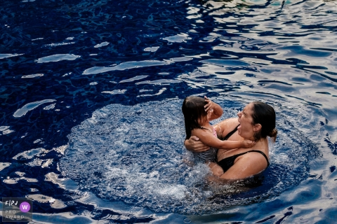 A mother and daughter come up for a breath of air in the pool in this photo by a Berlin, Germany family photojournalist.