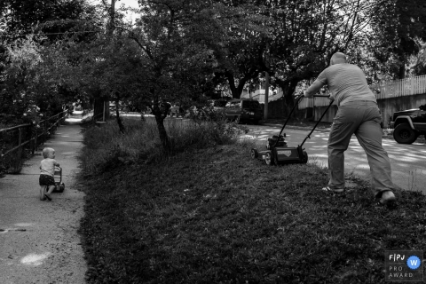 A little boy copies his father mowing the lawn as he pushes his own toy mower in this black and white photo by a British Columbia, Canada family photojournalist.