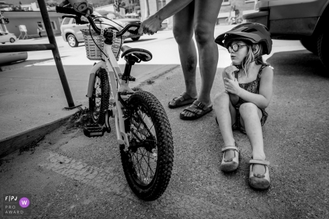 A little girl sits on the ground after falling off her bike in this black and white photo by a British Columbia, Canada family photojournalist.