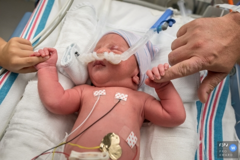 A newborn hooked up to monitors in the hospital holds its parents' fingers in each hand in this photo by a Connecticut birth photographer.