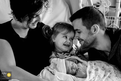 Groningen family photojournalist captured this black and white photo of a big sister meeting her sibling for the first time as mom and dad watch lovingly