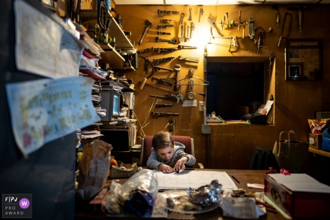 A boy writes on a table calendar in an office with tools covering the walls in this photo by a Madison, WI family photojournalist.