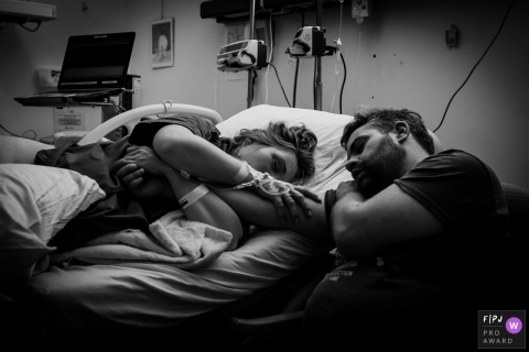 A wife holds her husbands arm as she lays in a hospital bed and the two of them sleep in this black and white photo by a Drenthe, Netherlands birth photographer.