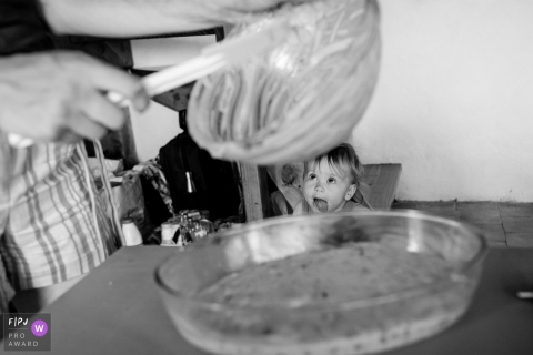 A little girl with her tongue sticking out watches her mother make food in the kitchen in this black and white photo by a Nantes family photojournalist.
