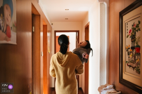 A baby boy cries in his mother's arms as she carries him down a hallway in this picture by a Zhejiang, China family photojournalist.