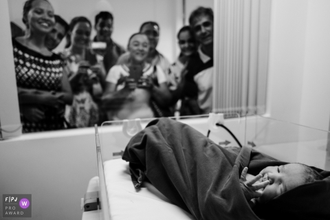 Family members look through the hospital window at their newest family member in this black and white photo by a Recife, Pernambuco birth photographer.
