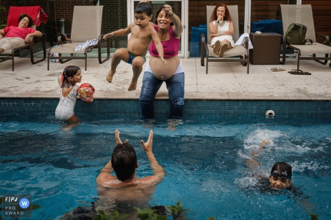 A mother tosses her son into a pool where his father waits to catch him in this image created by a Rio de Janeiro family photographer.