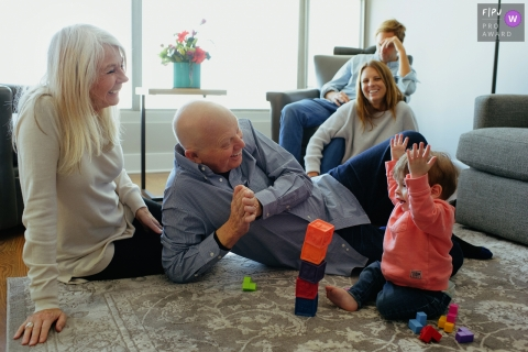 Grandparents sit on the floor watching their grandchild play with building blocks in this photograph by a Chicago, IL documentary family photographer.