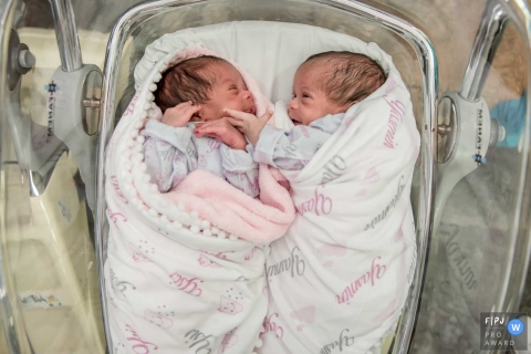 Newborn twins lay together in the hospital in this picture by a Rio de Janeiro, Brazil birthing photographer.