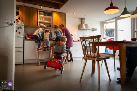 A girl rides a tricycle in the kitchen as three others help their mom with food in this photo by a Holland award-winning family photographer.