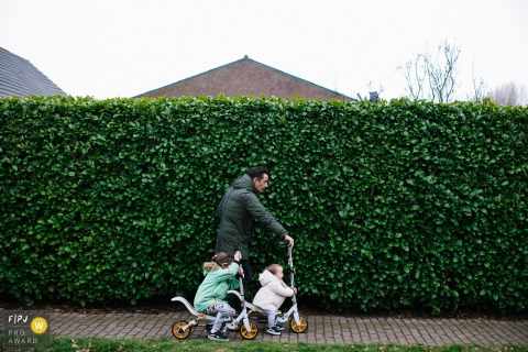Zuid Holland documentary family photographer captured this photo of a father leading two young children down the street on their bikes