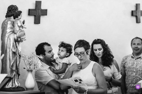 A family reads from a program in church in this black and white photo by a Paris family photographer.