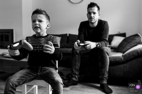 A father and son play video games together in this family picture by a Holland photographer.