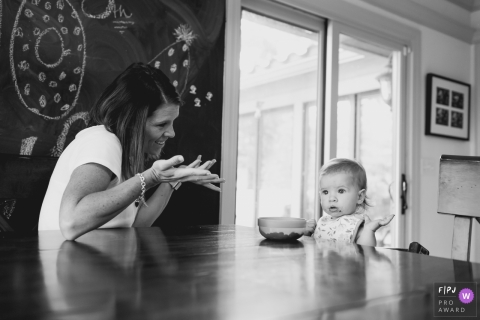 A mother shrugs at her baby girl who sits at the table not eating in this documentary-style family photo captured by a Kansas photographer.