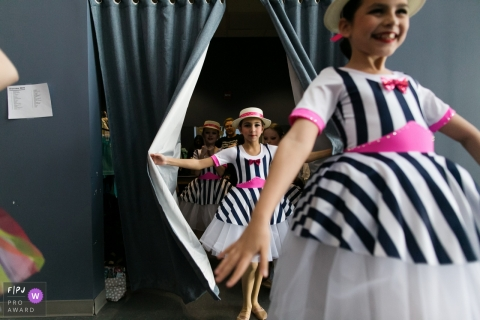 Girls in striped dresses emerge from behind a curtain in this photograph by an Overland Park, KS documentary family photographer.