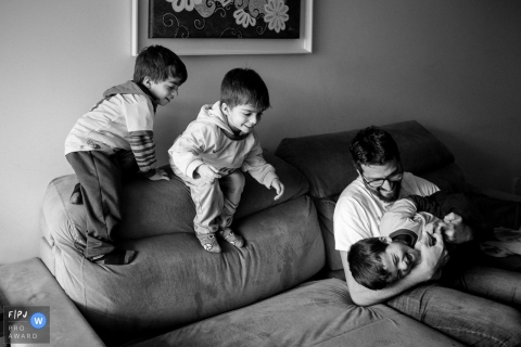 A father plays with his three sons on a couch in this photo recorded by a Santa Catarina award-winning, documentary-style family photographer.