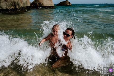 Une mère joue avec son fils dans les vagues de l'océan sur cette photo prise par un photojournaliste de la famille Santa Catarina.