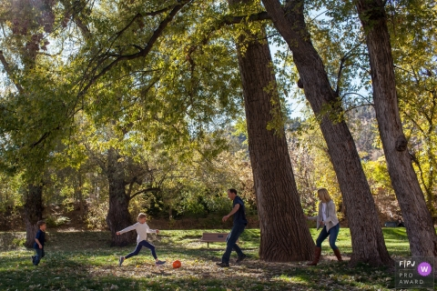 Two children and their parents play soccer in a park in this image created by a Boulder, CO family photographer.