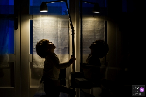 A boy plays with a lamp in a dark room in this picture captured by a Valencia, Spain family photojournalist.