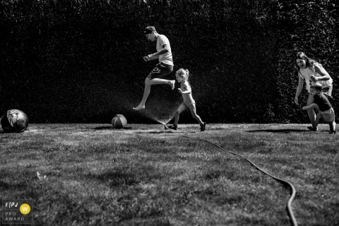 Eindhoven documentary family photographer captured this black and white photo of a family of four running through a sprinkler in their yard