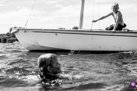 A little boy watches his sibling swim in the water from a sailboat in this black and white photo by an Eindhoven family photographer.