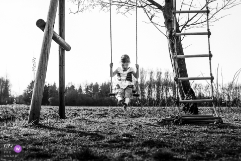 A little girl plays on a swing set outside in this black and white photo by an Eindhoven reportage family photographer.