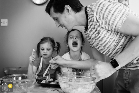 Cambridgeshire photo family journalist captured this black and white image of a father and his two children making cupcakes together