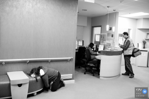 A man works on getting his wife checked into the hospital in this black and white photo by a Virginia award-winning birthing photographer.
