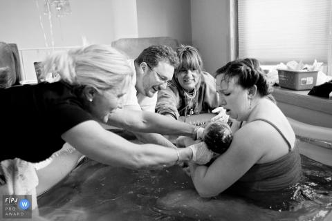 Une mère, un père et des infirmières tiennent son bébé nouveau-né dans une baignoire d'accouchement après sa naissance à la maison, sur cette photo en noir et blanc réalisée par un photographe de naissance de la famille Virginia.