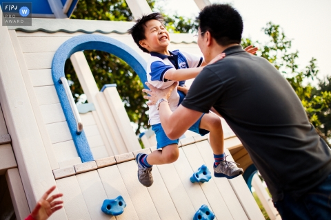 A boy jumps down from a play set into his father's arms in this photograph by a San Francisco, CA documentary family photographer.