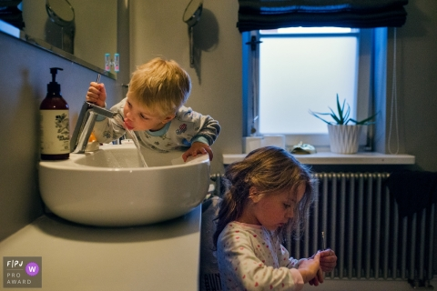 A little boy drinks from the bathroom faucet as his sister stands below him in this documentary-style family photo captured by a Warsaw photographer.