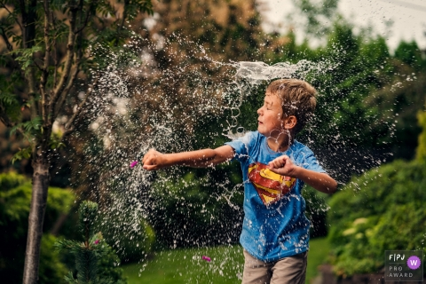 A boy has water splashed on him as he plays outside in this Family Photojournalist Association awarded photo by a Warsaw documentary family photographer.