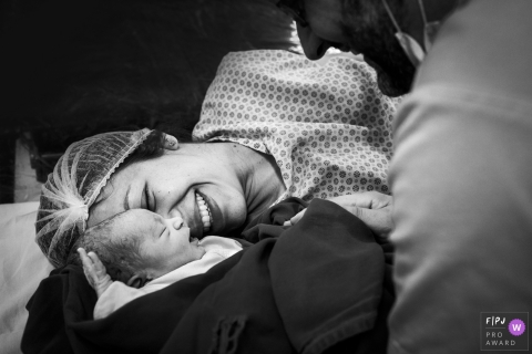A woman holds her baby for the first time in the hospital in this black and white photo by a Minas Gerais, Brazil reportage-style family birth photographer.