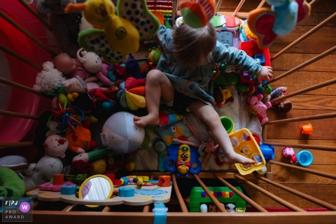 A little girl plays with the plethora of toys in her crib in this FPJA award-winning image captured by a Antwerpen family photographer.