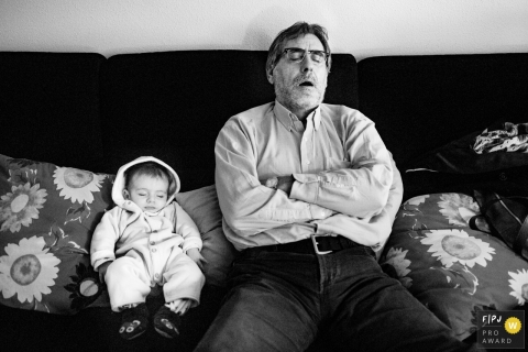 Valencia family photojournalist created this black and white image of an infant and grandfather sleeping peacefully on a couch