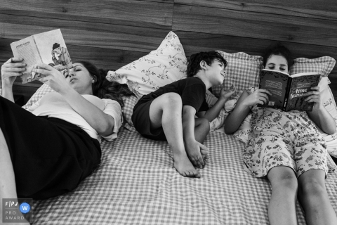 Two women sit in bed reading with a little boy between them in this award-winning photo by a Minas Gerais documentary family photographer.