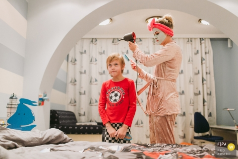 Saint-Petersburg documentary family photographer captured this photo of a mom dressed in pajamas and a face mask styling her child's hair in an ocean themed bedroom