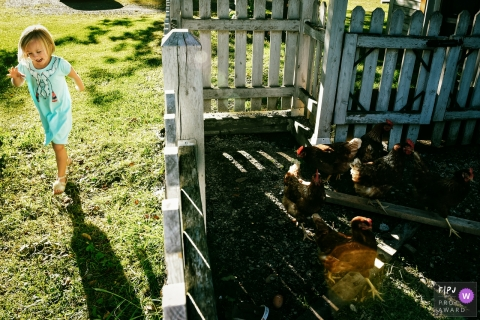 A girl plays outside next to a chicken pen in this documentary-style family image recorded by a Montreal, Quebec photographer.