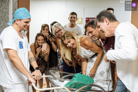 A family meets their newest member for the first time in the hospital in this awarded image by a Rio de Janeiro, Brazil birth and newborn photographer.