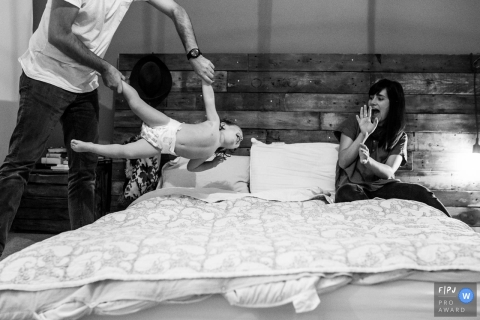 A father tosses his son onto a bed as his mother shields herself in this documentary-style family photo captured by a Essex, England photographer.