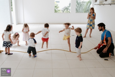 Several children play with a jump rope in this family picture by a Santa Catarina photographer.