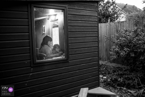 A mother and her little girl write together inside their house in this photograph by an Essex, England documentary family photographer.